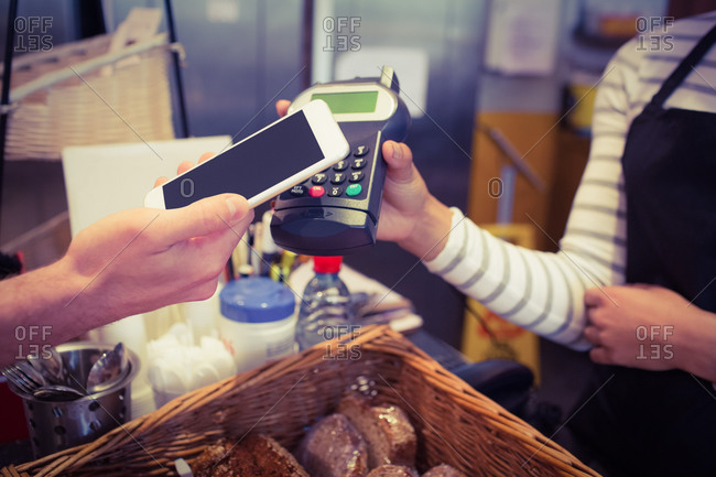 Customer paying with mobile phone at the cafe
