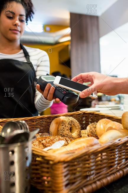 Customer paying with his cellphone at the cafe