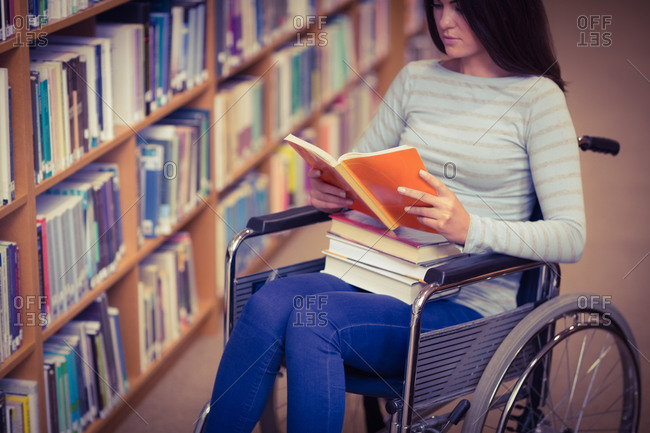 Mid section of disabled female student reading book on wheelchair in library