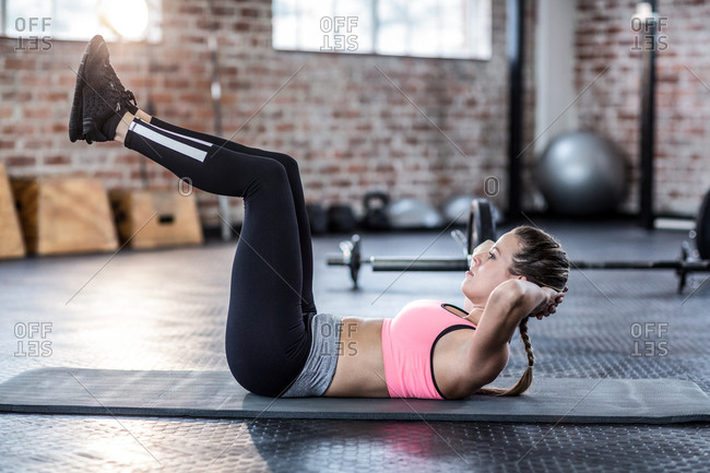 Woman doing stomach crunches on exercise mat the gym
