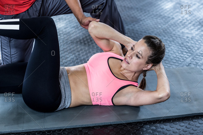 Male trainer assisting woman with abdominal crunches gym
