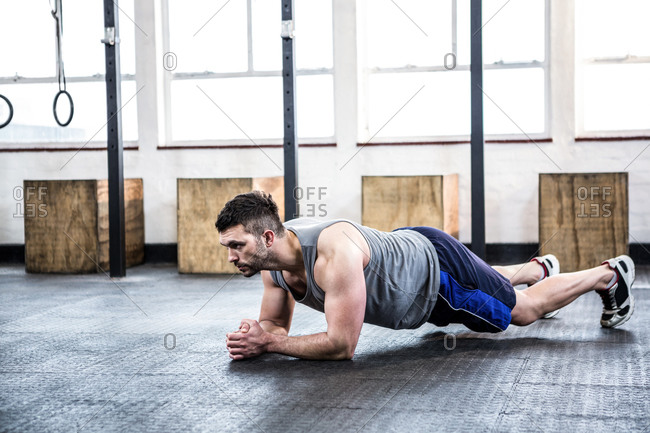 Fit man struggling in a plank position at the gym