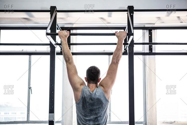 Fit man doing pull ups in a fitness studio