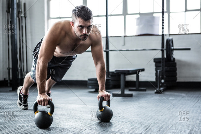 Fit shirtless man in plank on kettlebells