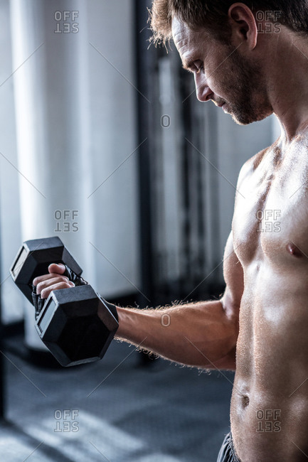 Shirtless man lifting heavy black dumbbell at the gym