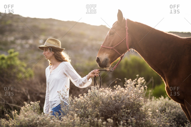 Young woman walking with her horse in the countryside