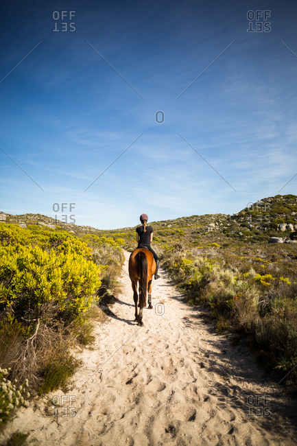Rear view of a  woman riding her horse in the countryside