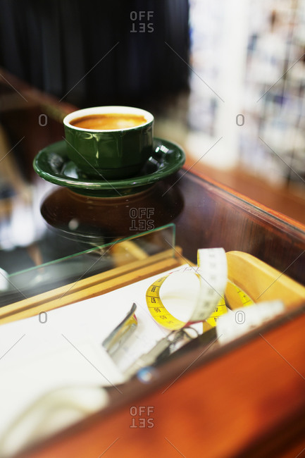 Cup of coffee and measuring tape on counter