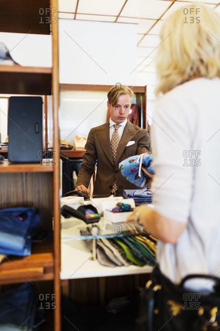 Woman making purchase in men's formalwear store