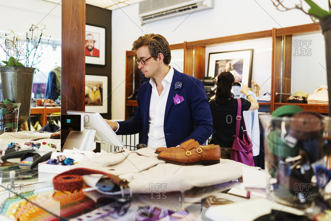 Man ringing up purchases in formalwear store