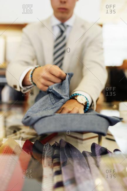 Clerk folding up a dress shirt in shop
