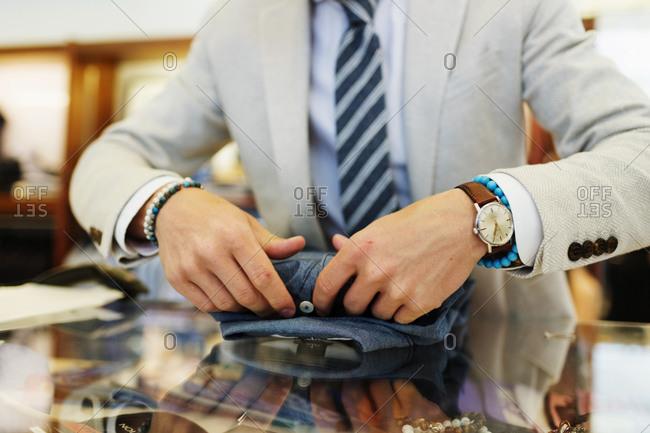 Clerk folding up a dress shirt in store