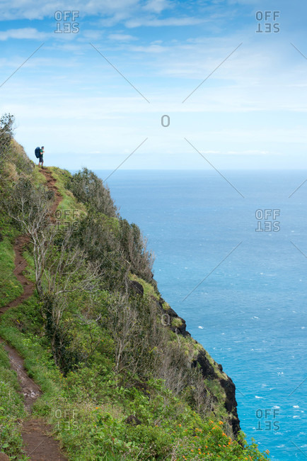 Hiker on Kalalau Trail along Kauai's Napali Coast in Hawaii