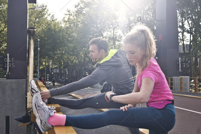 Man and woman stretching on a bridge for run