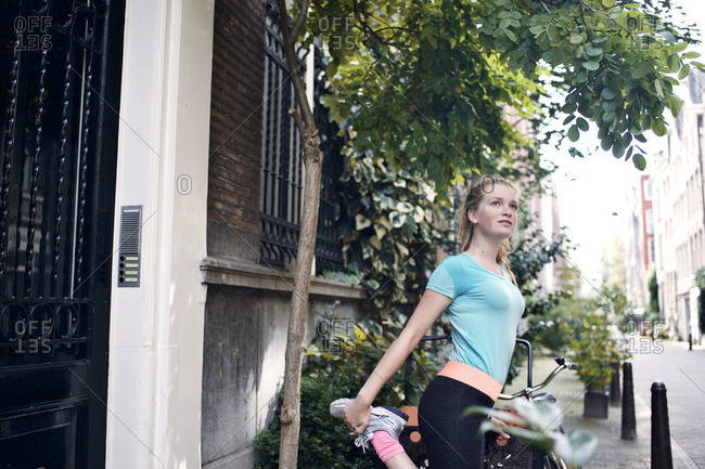 Female runner stretching her thighs on city street