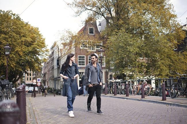 Cool couple walking over canal bridge