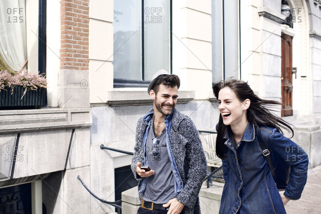 Stylish couple laughing and walking in city street