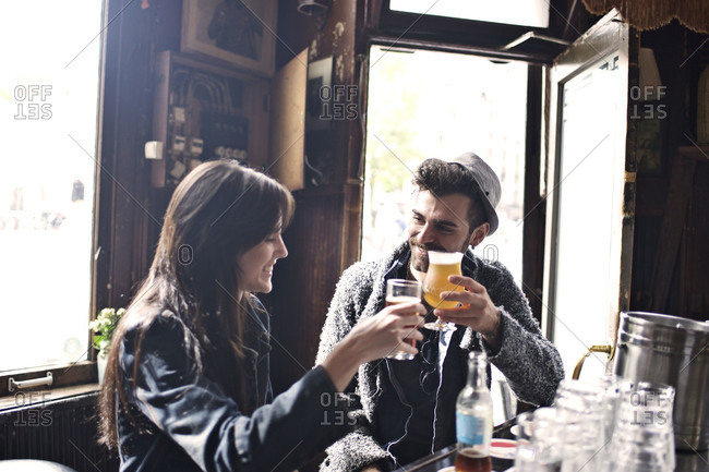 Man and woman chatting in a bar with drinks