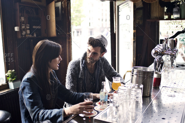 Couple talking over drinks in bar