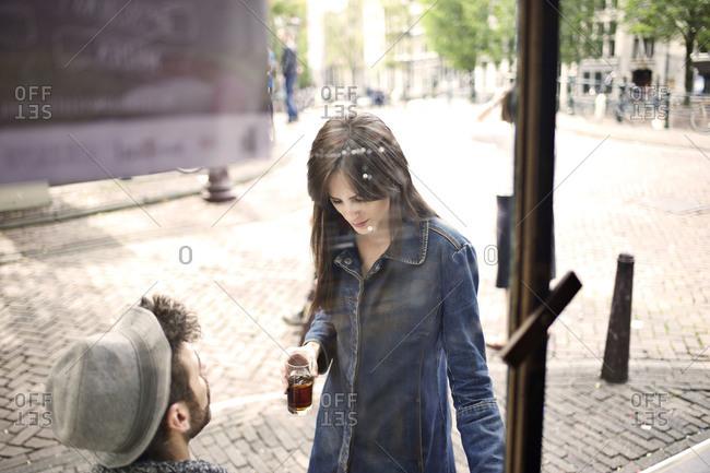 Woman sitting down next to man outside bar