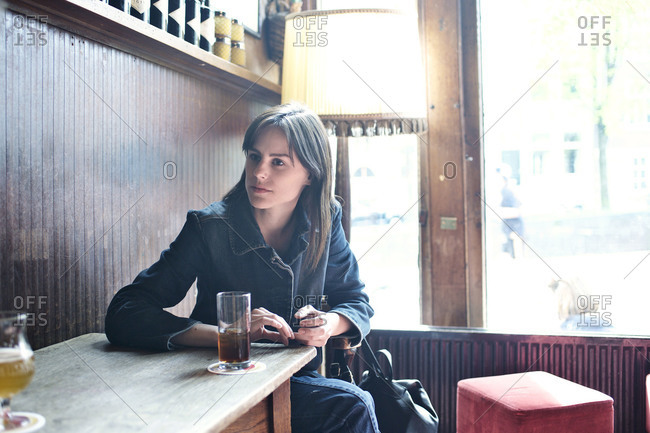 Woman sitting at bar table listening