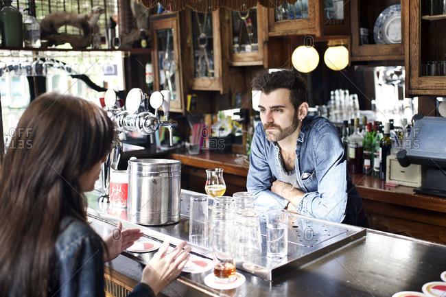 Male bartender listening to female patron