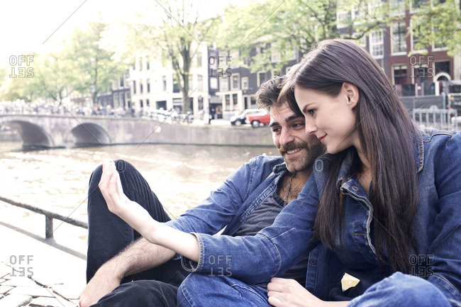 Couple taking selfie next to a canal