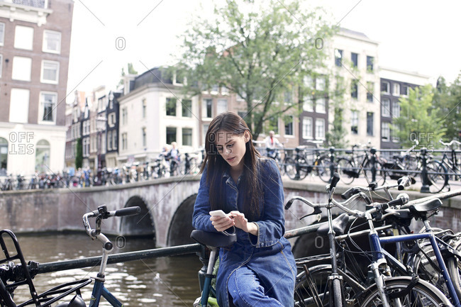 Woman with smartphone next to canal