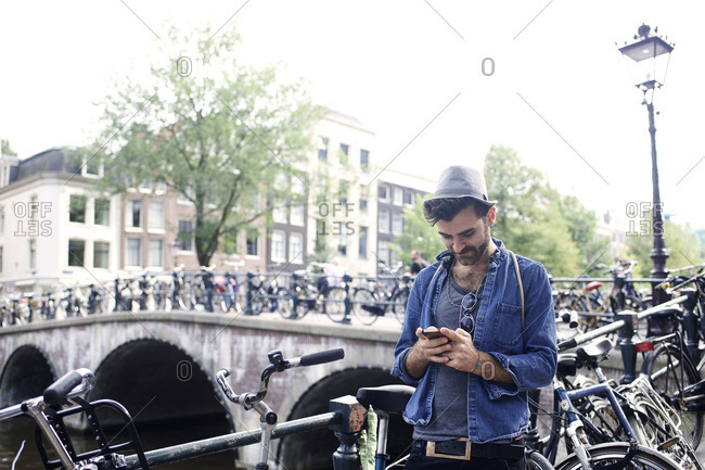 Man with smartphone next to canal