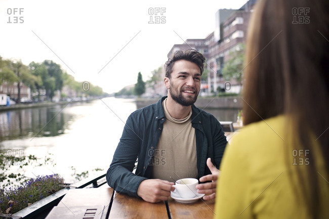 Man chatting with friends at a canalside cafe in Amsterdam