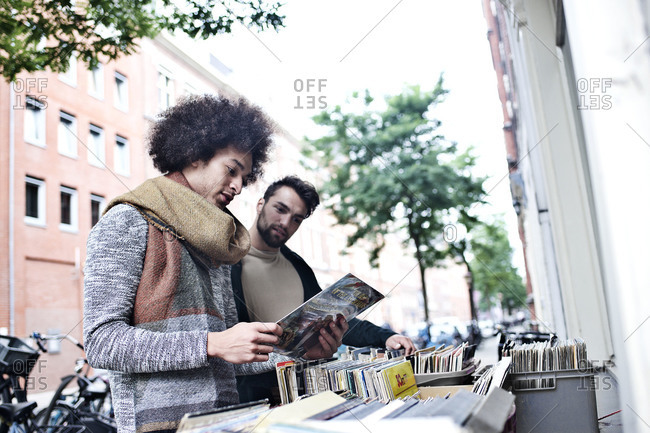 Two men checking out used records from bins in front of store