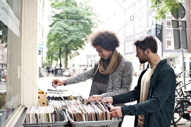 Two men shopping for used records at storefront