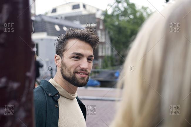 Bearded young man talks to woman on European street