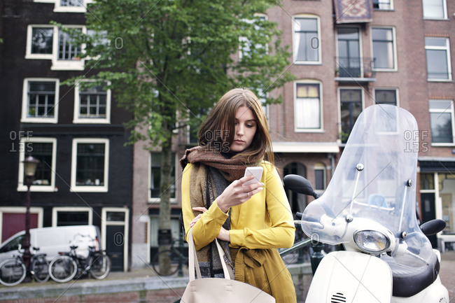 Woman using her smartphone while standing next to scooter on Amsterdam street