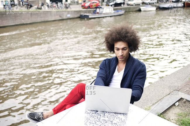 Elevated view of man using laptop outdoors along Amsterdam canal
