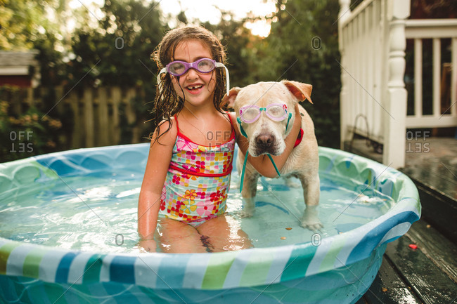 Girl and her dog wearing goggles in a pool