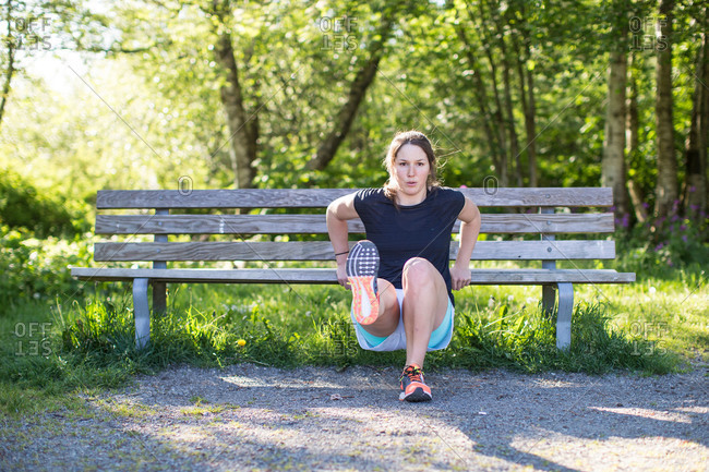 Woman doing workouts with bench in park
