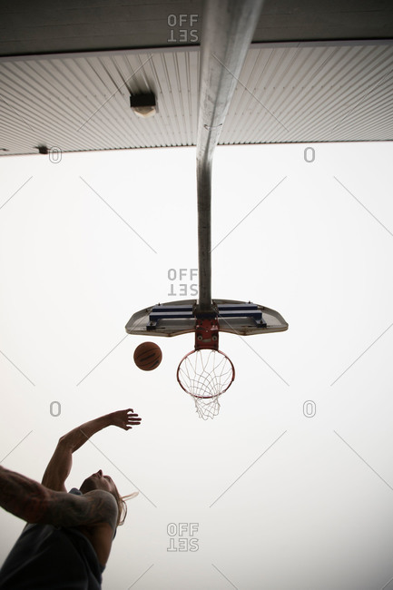 Man midair throwing basketball