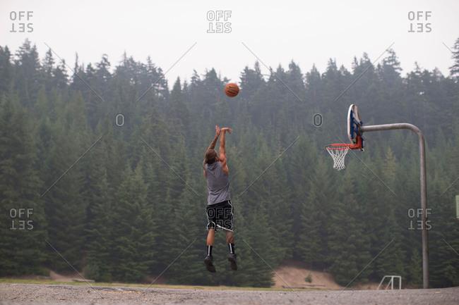 Man midair dunking a basketball in rural setting