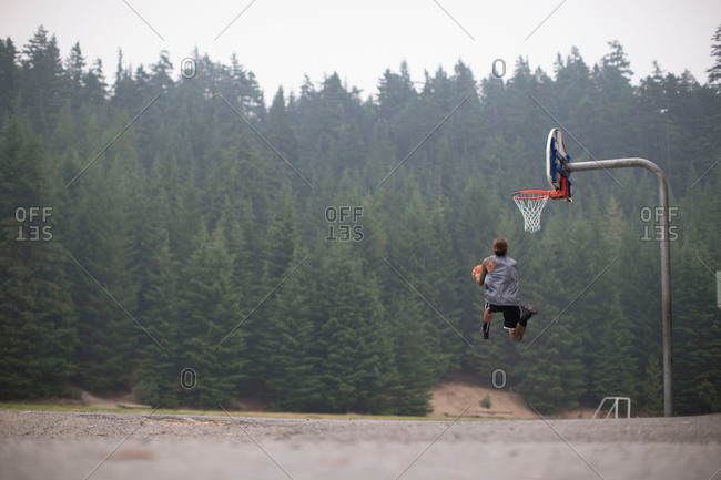 Man midair dunking basketball in rural setting