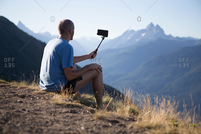 Man on mountainside using selfie stick