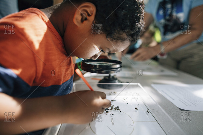 Boy looking through magnifying glass in classroom