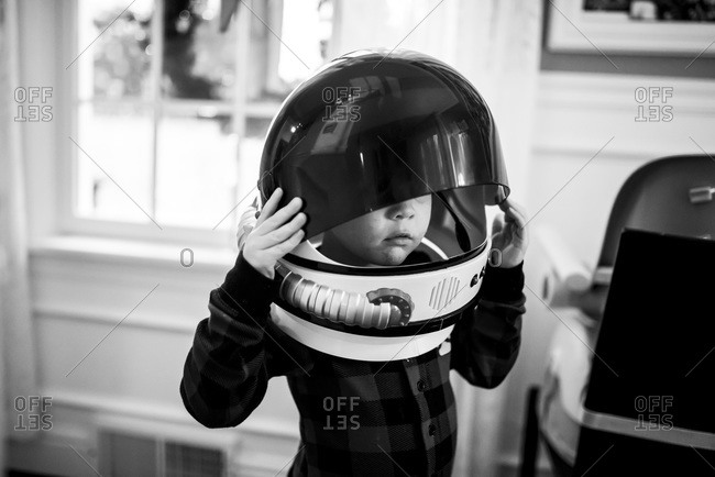 A child tries on a space helmet costume