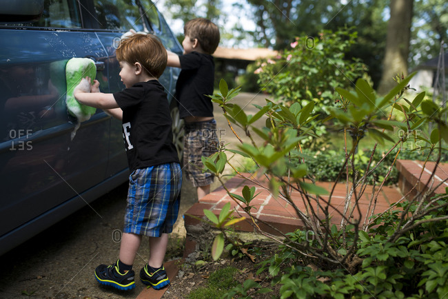 Two boys wash a car with soapy sponges