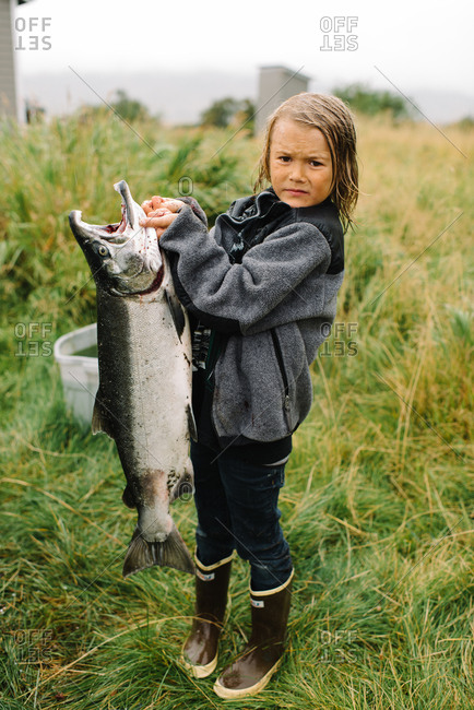 Boy holding a big fish she caught