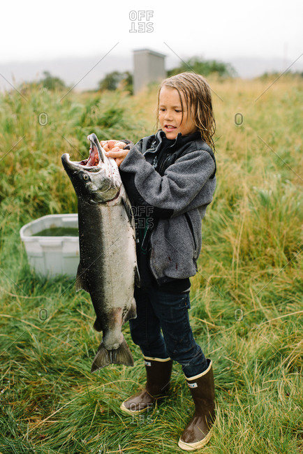 Boy holding a very big fish he caught
