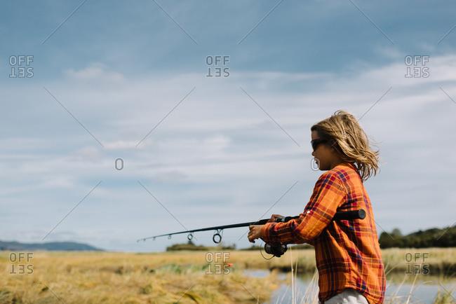 Boy reeling in his fishing line