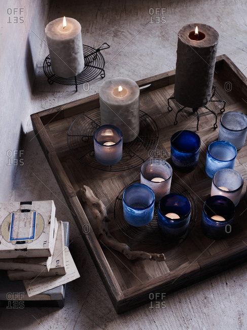 Various candles on a tray on ground