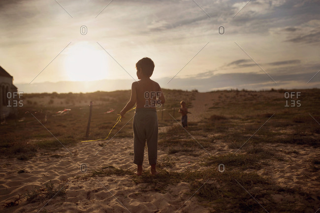 Boys playing on beach dunes at sunset