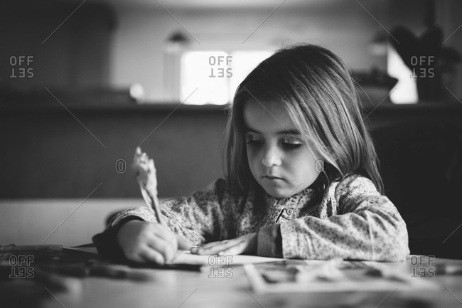 Girl with glitter eye shadow writing at a table